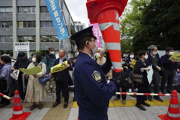 Un policía y varios manifestantes en contra de los planes del Gobierno japonés. - Sputnik Mundo