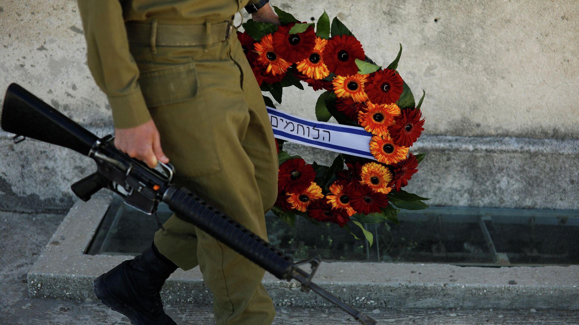 Un soldado con su arma y una corona de flores durante el Día de los Caídos, el 14 de abril de 2021 - Sputnik Mundo, 1920, 14.04.2021