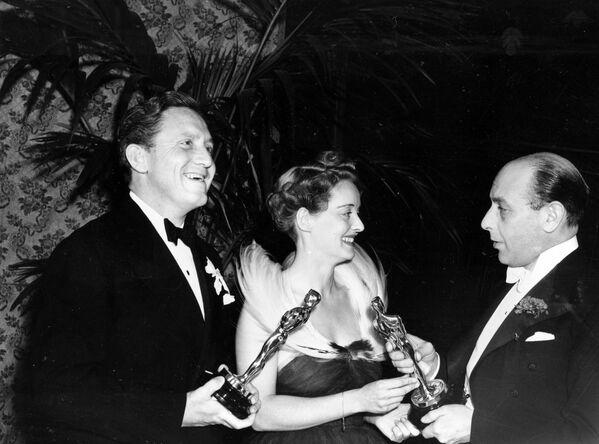El actor británico Sir Cedric Hardwicke (derecha) presenta el Premio Oscar a Bette Davis y Spencer Tracy (izquierda), 1938 - Sputnik Mundo