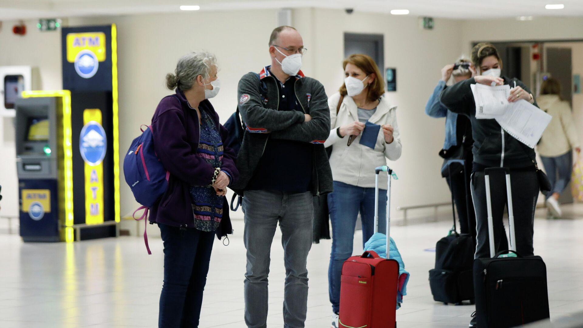 Turistas con mascarillas en un aeropuerto - Sputnik Mundo, 1920, 14.04.2021