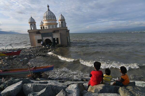 Unos niños esperan el final de su ayuno diario durante el mes sagrado del Ramadán frente a una mezquita en Palu (Indonesia). - Sputnik Mundo