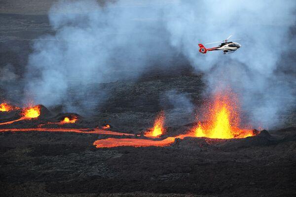 Un helicóptero sobrevuela la lava que fluye desde el volcán Piton de la Fournaise en la isla de Reunión. - Sputnik Mundo