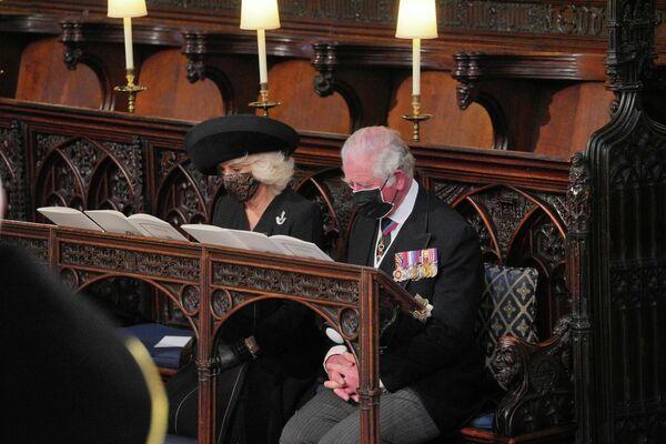 La familia real cumple estrictamente las restricciones de COVID-19 durante el funeral del príncipe Felipe. Todos los invitados se colocaron la mascarilla en el interior de la iglesia.En la foto: príncipe Carlos de Gales y duquesa de Cornualles, Camila. - Sputnik Mundo