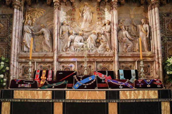 La familia real británica estará de luto durante dos semanas después de la muerte del príncipe. El luto será respetado también por su personal, así como por las unidades militares especiales que realizan tareas ceremoniales.En la foto: las insignias del duque de Edimburgo en el altar de la capilla de San Jorge. - Sputnik Mundo