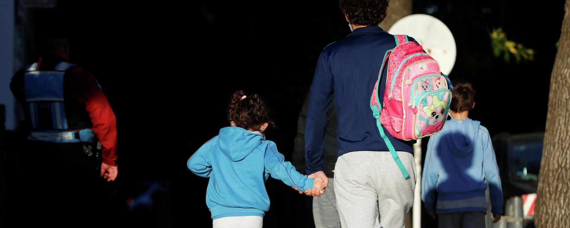 Un hombre lleva a su hija a la escuela en Buenos Aires - Sputnik Mundo, 1920, 19.04.2021