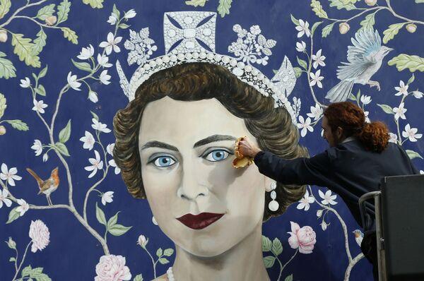 Unos obreros instalan un mural de Frederick Wimsett que representa a Isabel II en la víspera de su 90 cumpleaños, en el centro de Londres. - Sputnik Mundo