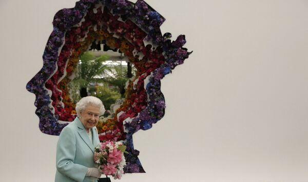 Isabel II junto a su retrato durante una visita al Festival de Flores de Chelsea, en Londres. - Sputnik Mundo