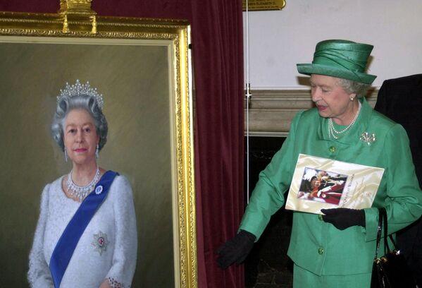 Isabel II junto a un retrato obra del artista Theodore Ramos en el Castillo de Windsor, en el Reino Unido. - Sputnik Mundo
