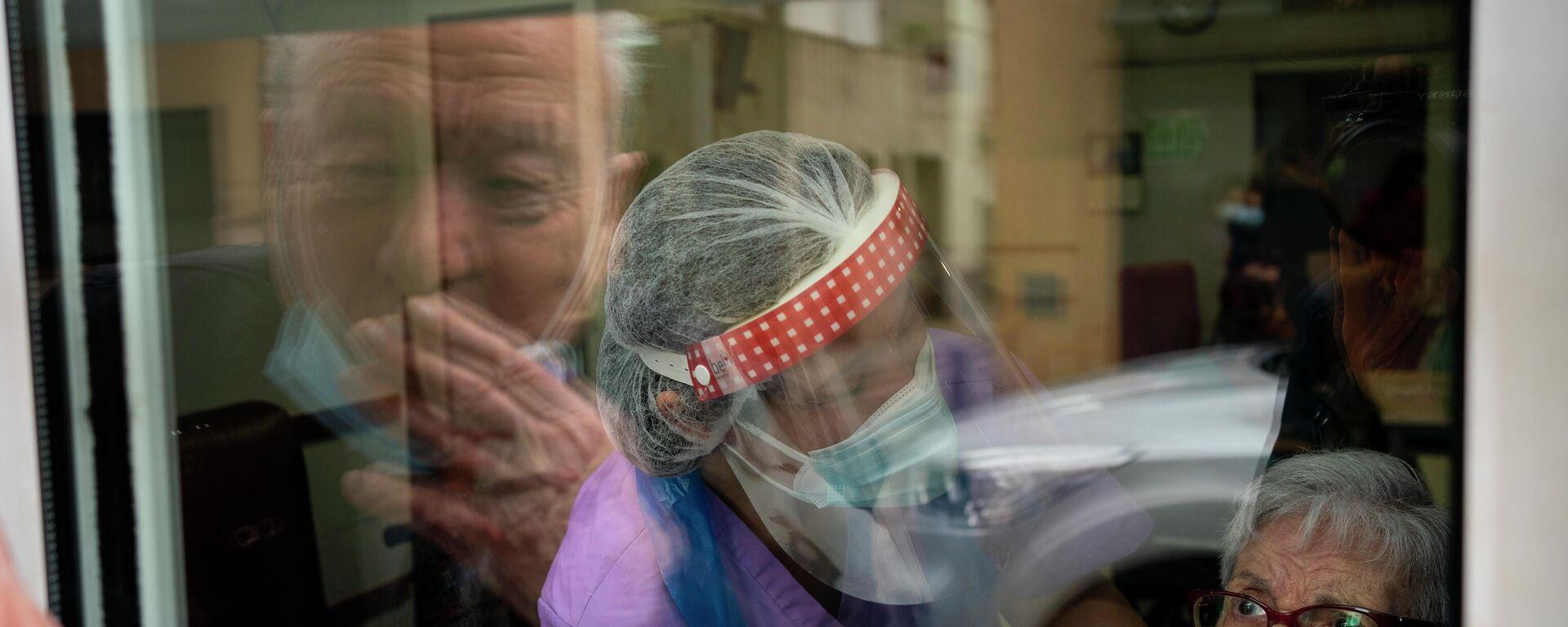 Javier Anto y su esposa Carmen Panzano se lanzan besos a través de la ventana. Barcelona, 21 de abril de 2021.  - Sputnik Mundo, 1920, 22.04.2021