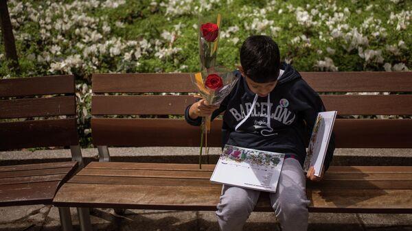 Un chico sostiene una rosa y un par de libros en el Día de Sant Jordi, Barcelona - Sputnik Mundo