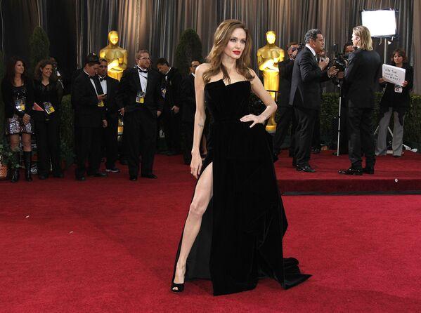 El elegante vestido de terciopelo de Versace, en el que Angelina Jolie llegó a la ceremonia de los Oscars de 2012 junto a Brad Pitt, se convirtió en fuente inagotable de memes. La razón de las bromas en las redes fue el hecho de que la actriz no dejó de exhibir exageradamente su pierna derecha a través de la abertura del atuendo negro. - Sputnik Mundo