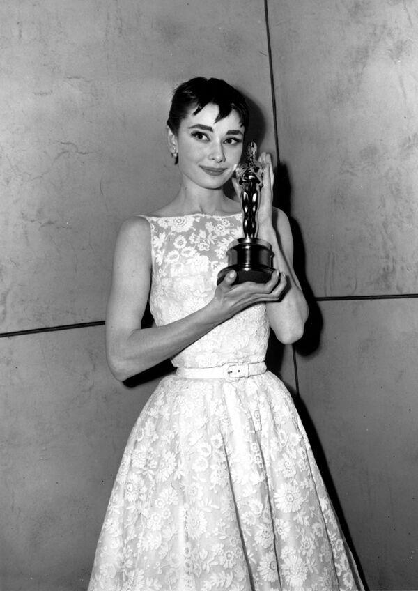 Un elegante vestido, creado por la diseñadora de vestuario Edith Head para el personaje de Audrey Hepburn en la película Vacaciones en Roma, le gustó tanto a la estrella que decidió usar un atuendo similar para recibir su Óscar a la mejor actriz en 1954. El vestido, firmado por Hubert Givenchy, ahora se considera uno de los clásicos del siglo XX. - Sputnik Mundo