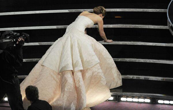 El blanco de los memes en la premiación del año siguiente fue Jennifer Lawrence, pues se cayó al subir las escaleras del escenario para recibir su Óscar a la mejor actriz. La probable razón de su resbalón fue la larga cola de su vestido Dior. El atuendo, cuya etiqueta de precio alcanzaba los cuatro millones de dólares, es el más caro que haya cruzado la alfombra roja del premio cinematográfico. - Sputnik Mundo