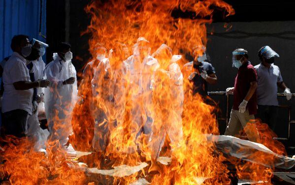Familiares de un fallecido a causa del coronavirus en una pira funeraria de Nueva Delhi (la India). - Sputnik Mundo
