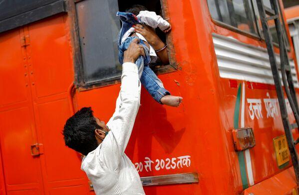 Un trabajador migrante pasa a su hijo a través de la ventana de un autobús en Ghaziabad (la India) al regresar a su aldea, después de que el gobierno de Nueva Delhi decretara un cierre de seis días en un intento de contener la propagación del COVID-19. - Sputnik Mundo