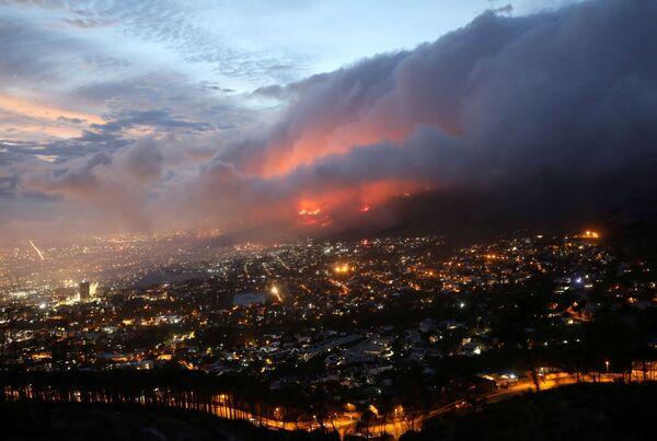 Las llamas de un incendio forestal iniciado en las laderas de la montaña de la Mesa se acercan a las residencias en la Ciudad del Cabo (Sudáfrica) el 19 de abril. - Sputnik Mundo