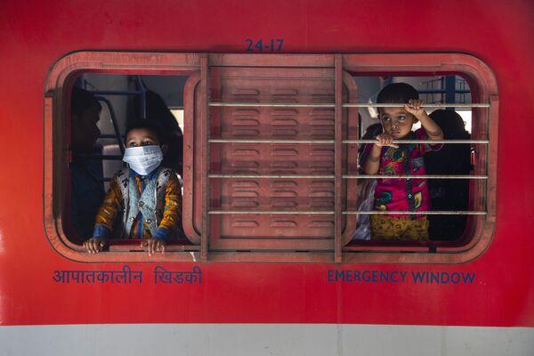 Unos niños miran desde la ventana de un tren en una estación de tren en Gauhati (la India). - Sputnik Mundo