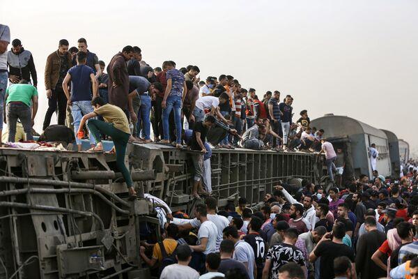 Unas personas suben a un vagón volcado en el lugar de un accidente de tren en la ciudad egipcia de Toukh. - Sputnik Mundo