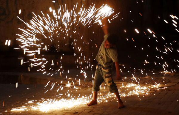 Un joven juega con fuegos artificiales mientras celebra el Ramadán en la ciudad de Gaza. - Sputnik Mundo