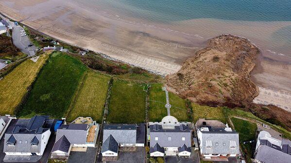 Unas casas en el borde de un acantilado después de que este se derrumbara parcialmente en la aldea de Nefyn, Gales (Reino Unido). - Sputnik Mundo