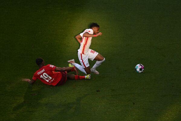 El defensor holandés del Colonia, Kingsley Ehizibue, y el centrocampista francés del Leipzig, Christopher Nkunku, disputan el balón durante un partido de la Bundesliga, la primera división del fútbol alemán. - Sputnik Mundo