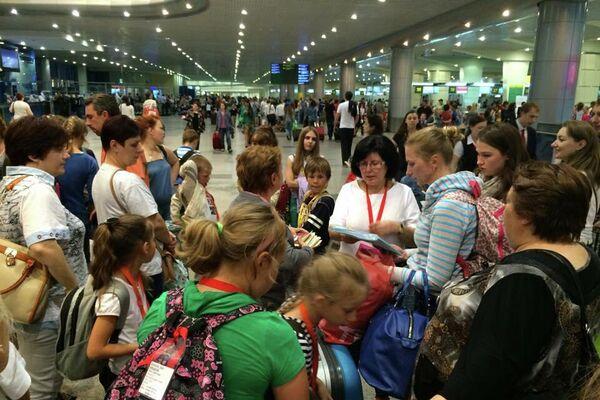 Los niños de Chernóbil con sus familias rusas en el aeropuerto Domodedovo de Moscú antes de ir a Galicia con Ledicia Cativa - Sputnik Mundo