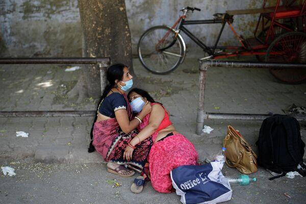 Una mujer sostiene a su familiar en la calle en medio de la crisis sanitaria en la India. - Sputnik Mundo