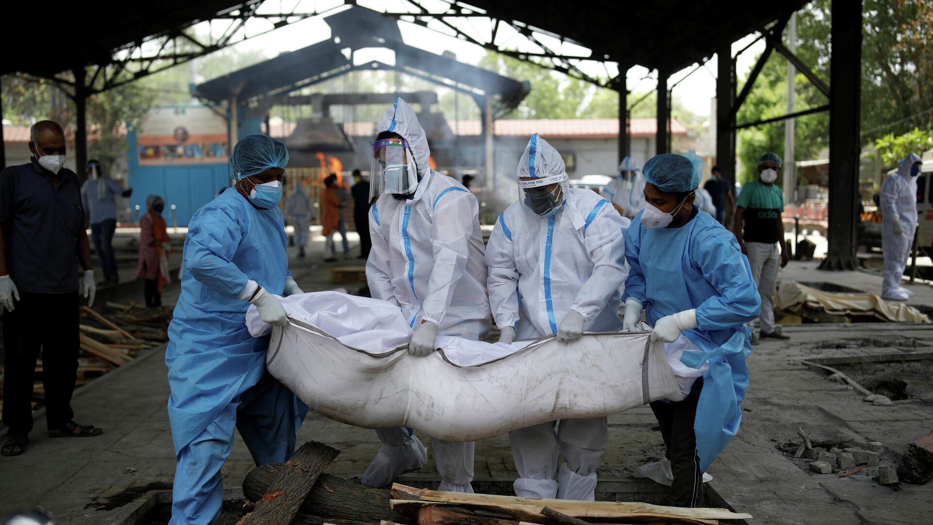 Varias personas con trajes de bioseguridad evacúan a las personas que fallecieron por coronavirus en la India - Sputnik Mundo, 1920, 28.04.2021