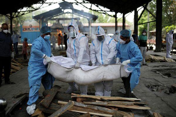 Varias personas con trajes de bioseguridad evacúan a las personas que fallecieron por coronavirus en la India. - Sputnik Mundo