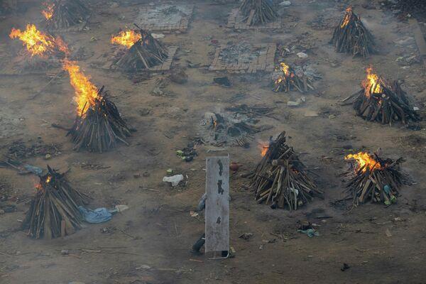 Varias piras funerarias en el terreno de un crematorio en Nueva Delhi. - Sputnik Mundo