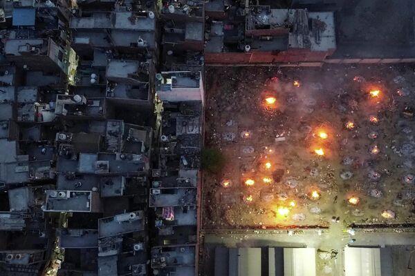 Una vista aérea de las piras funerarias cerca de un barrio en Nueva Delhi, India. - Sputnik Mundo