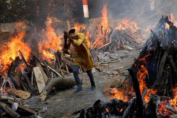 Según los datos oficiales, el número total de personas infectadas en India ha superado los 17,6 millones. Muchos hospitales se están quedando sin espacio y sin oxígeno médico, lo que provoca la muerte de los pacientes.En la foto: una cremación masiva de los muertos del COVID-19 en Nueva Delhi. - Sputnik Mundo