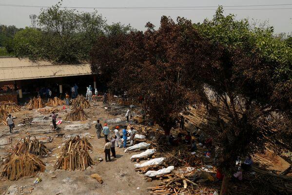 Las tradiciones indias prevén la cremación, pero no de esta forma. Normalmente, los muertos son llevados a estructuras especiales en las orillas de los ríos sagrados y se utiliza la leña de ciertos árboles.En la foto: preparación de las hogueras para una cremación masiva de los muertos del COVID-19 en Nueva Delhi. - Sputnik Mundo