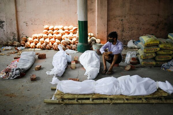 Un hombre está sentado junto a los cuerpos de los muertos por el COVID-19 antes de una cremación masiva en Nueva Delhi. - Sputnik Mundo