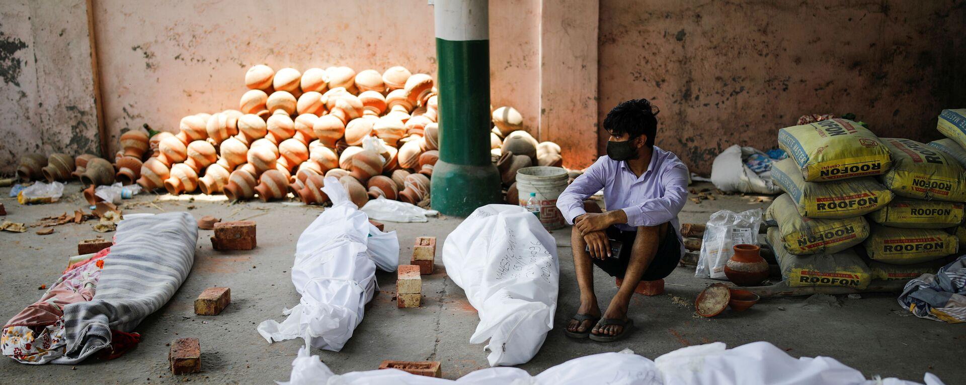 Мужчина сидит рядом с телами умерших от коронавируса перед массовой кремацией в крематории Нью-Дели, Индия - Sputnik Mundo, 1920, 15.05.2021