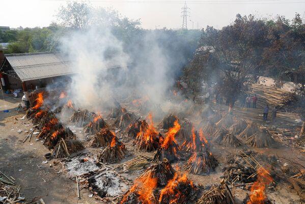 Una peregrinación masiva de varias semanas durante el Kumbhamela, el festival sagrado del cántaro, una de las fiestas religiosas más importantes y concurridas de la India, también contribuyó al brote de la enfermedad.En la foto: una vista aérea de una cremación masiva en Nueva Delhi. - Sputnik Mundo