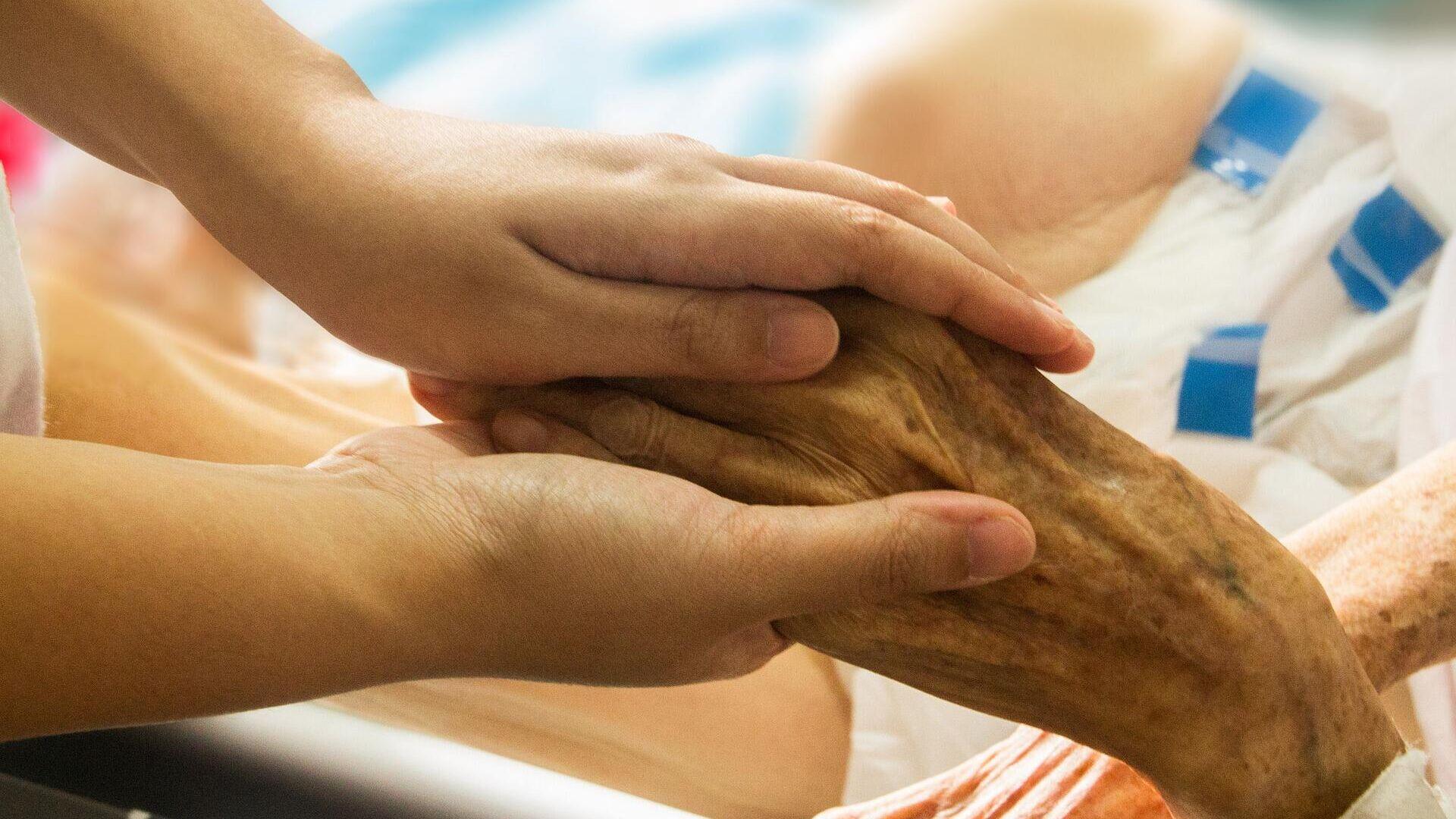 Una persona sosteniendo la mano de un paciente - Sputnik Mundo, 1920, 25.06.2021