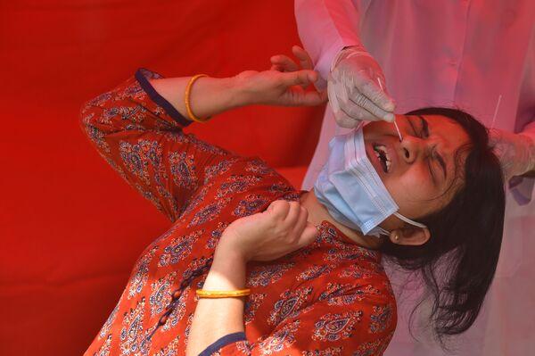 Durante lo que llevamos de pandemia han sido ya 18,3 millones los casos de coronavirus registrados. El número oficial de víctimas es superior a 200.000. En la foto: una mujer joven se somete a la prueba de COVID-19 en un centro de pruebas en Delhi. - Sputnik Mundo