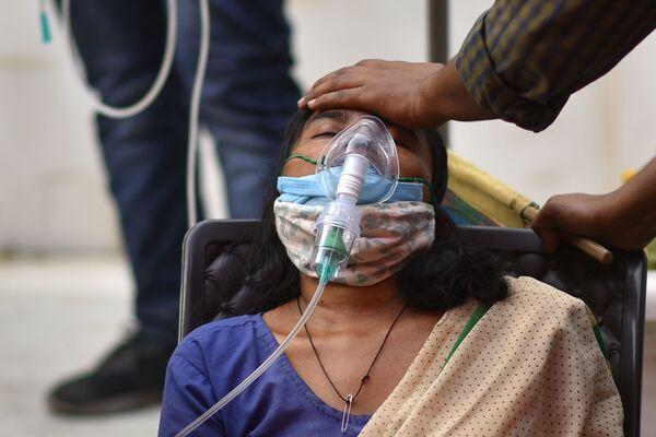 Tras los primeros éxitos en la lucha contra el COVID-19, el segundo país con más habitantes del mundo experimentó un rápido retroceso, y empezó a empeorar. Ahora, se detectan diariamente más de 350.000 contagios. En la foto: una mujer con problemas para respirar recibe oxígeno en el principal templo sij de la ciudad de Delhi, el Gurdwara Bangla Sahib. - Sputnik Mundo