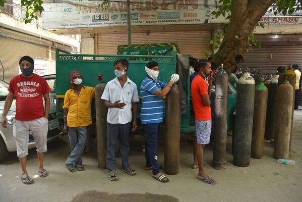 Ahora se permiten usar tanques de oxígeno, que se han convertido en el artículo más escaso, solo con fines médicos. En la foto: una cola cerca de la estación de recarga de cilindros de oxígeno medicinal en Delhi. - Sputnik Mundo