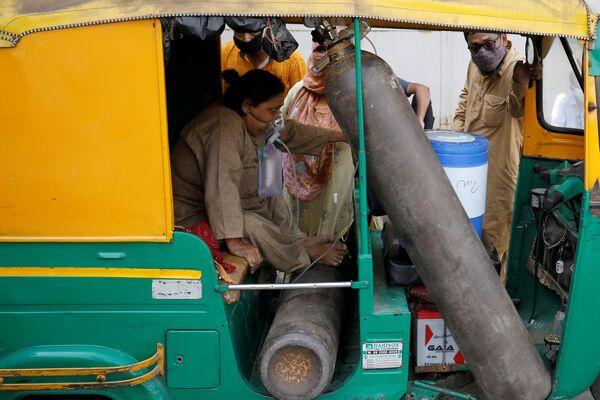 Una mujer con una máscara de oxígeno espera su turno para ser hospitalizada en la ciudad de Ahmedabad.  - Sputnik Mundo