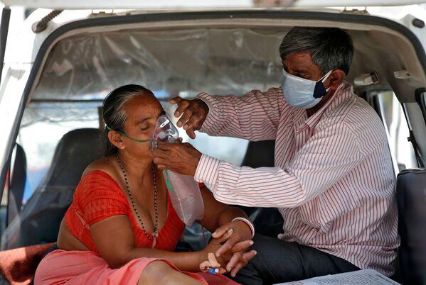 """La alta probabilidad de aparición de nuevas cepas de coronavirus más peligrosas en la India genera más preocupación. """"La numerosa población y su densidad es una incubadora perfecta para que este virus experimente con sus mutaciones"""", opina el profesor de Microbiología Clínica de la Universidad de Cambridge Ravi Gupta. En la foto: una pareja contagiada espera a ser hospitalizada en la ciudad de Ahmedabad. - Sputnik Mundo"""