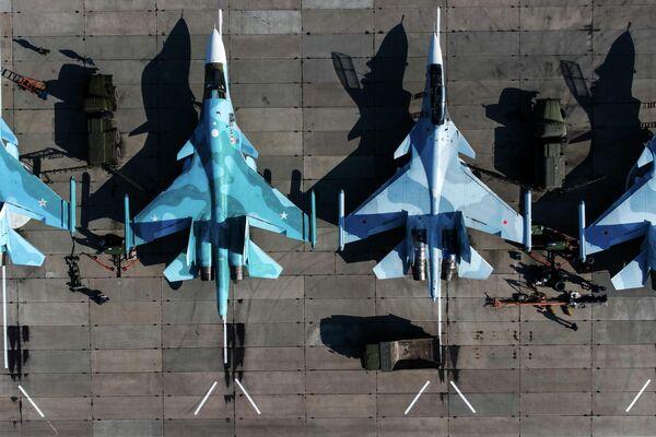 Unos cazabombardero SU-34 (a la izquierda) y cazas multipropósito Su-30SM (a la derecha) de las Fuerzas Aeroespaciales de Rusia - Sputnik Mundo