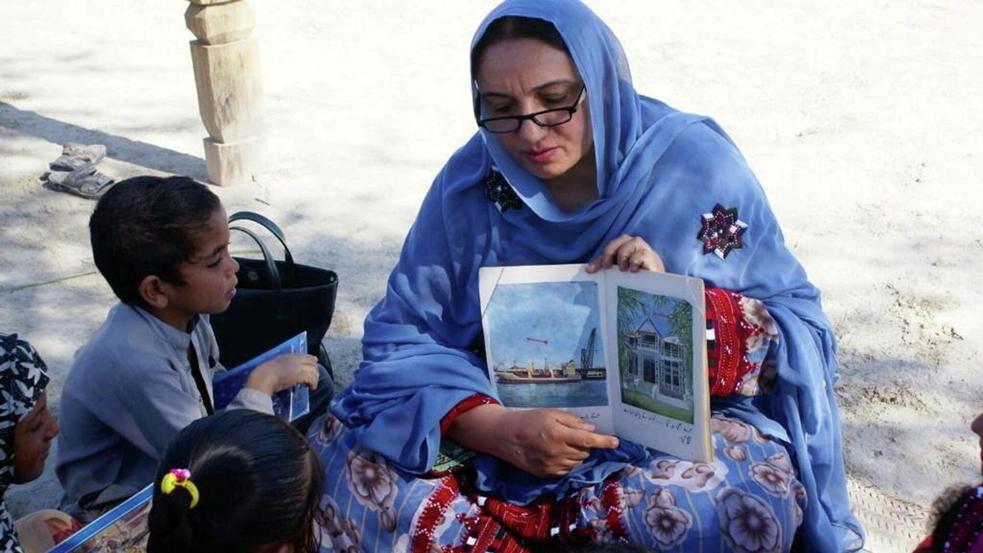 Los niños escuchan a una mujer leyendo un libro traído por el camello Roshan  - Sputnik Mundo, 1920, 29.04.2021