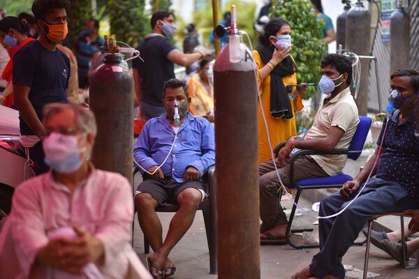 Personas con dificultad respiratoria reciben oxígeno medicinal de forma gratuita en un templo sij de Gurudwara, en Nueva Dehli, la India. - Sputnik Mundo