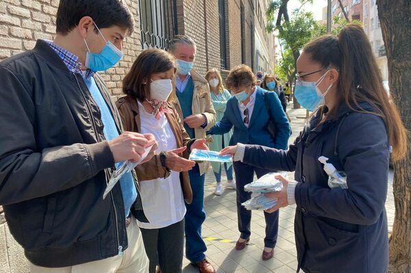 Reparto de mascarillas en la cola para votar en las elecciones a la Comunidad de Madrid. - Sputnik Mundo