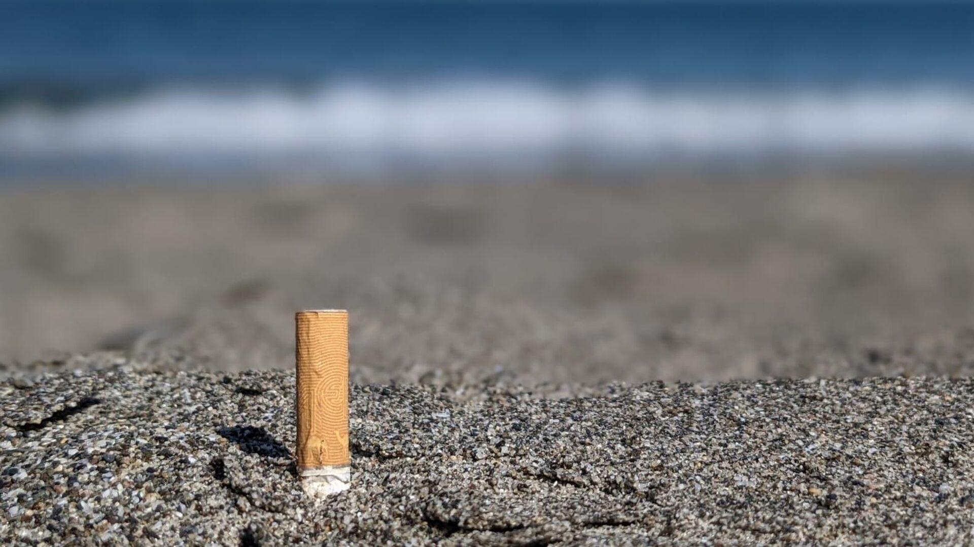 Imagen referencial de una colilla en la playa - Sputnik Mundo, 1920, 04.05.2021