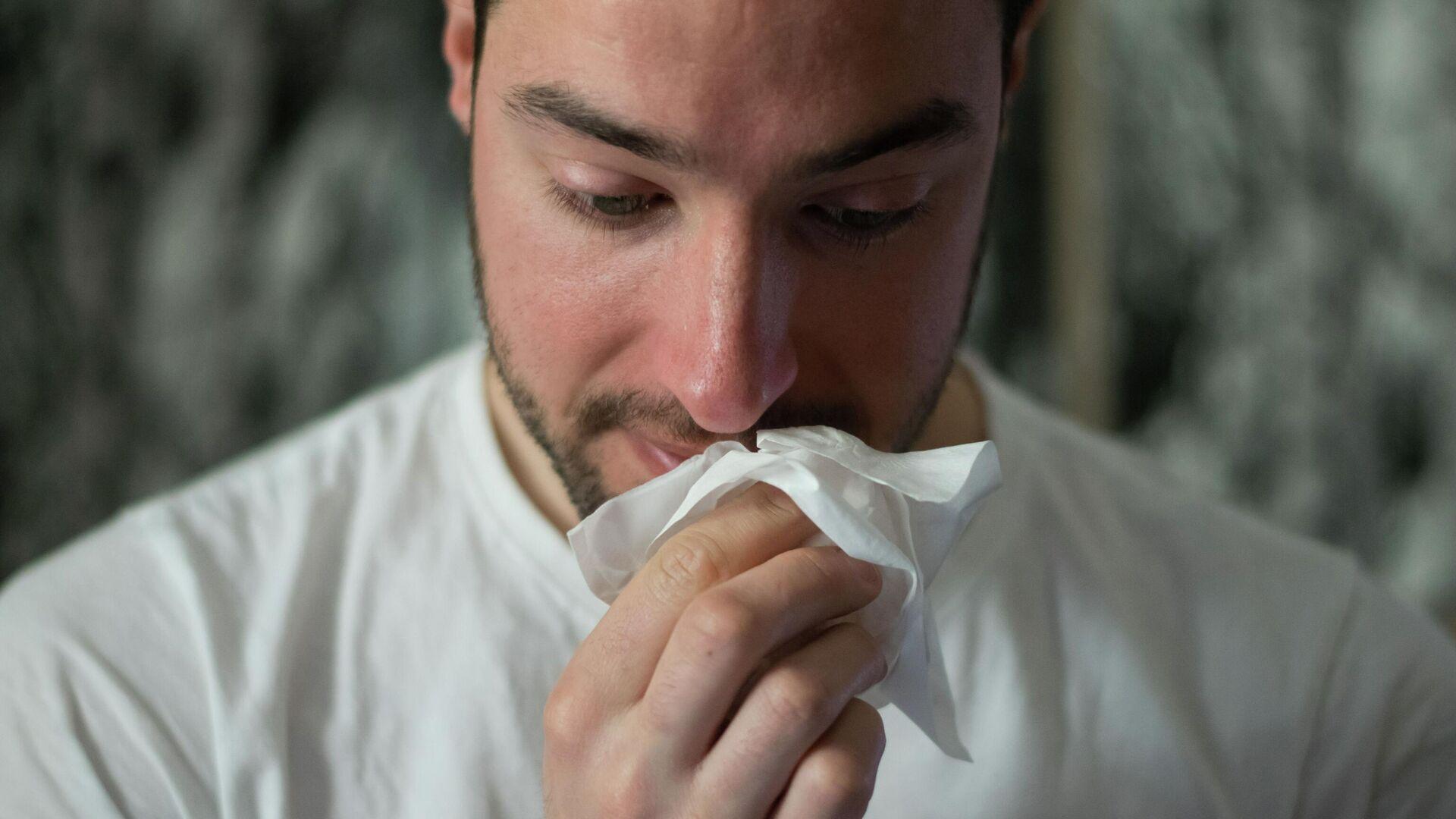 Un hombre se limpia la nariz con un pañuelo de papel - Sputnik Mundo, 1920, 04.05.2021
