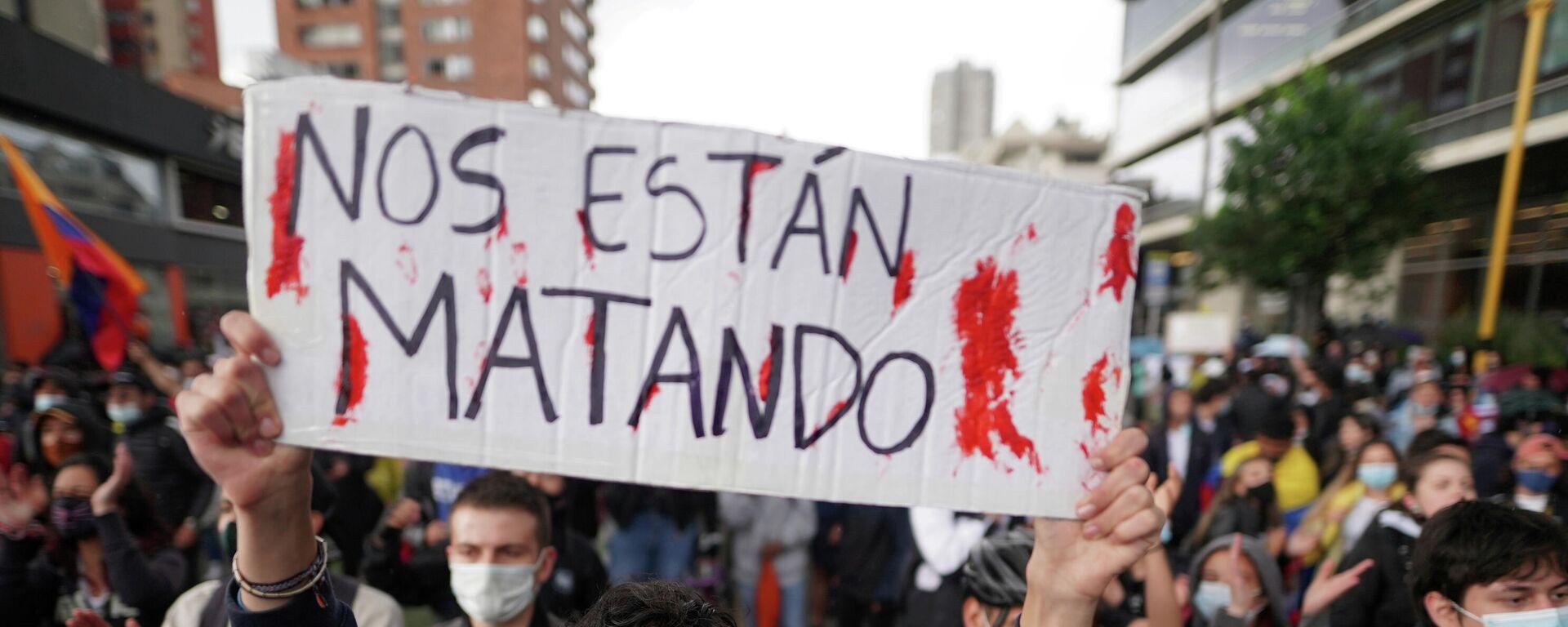 Un manifestante colombiano con un cartel que dice nos están matando. - Sputnik Mundo, 1920, 06.05.2021