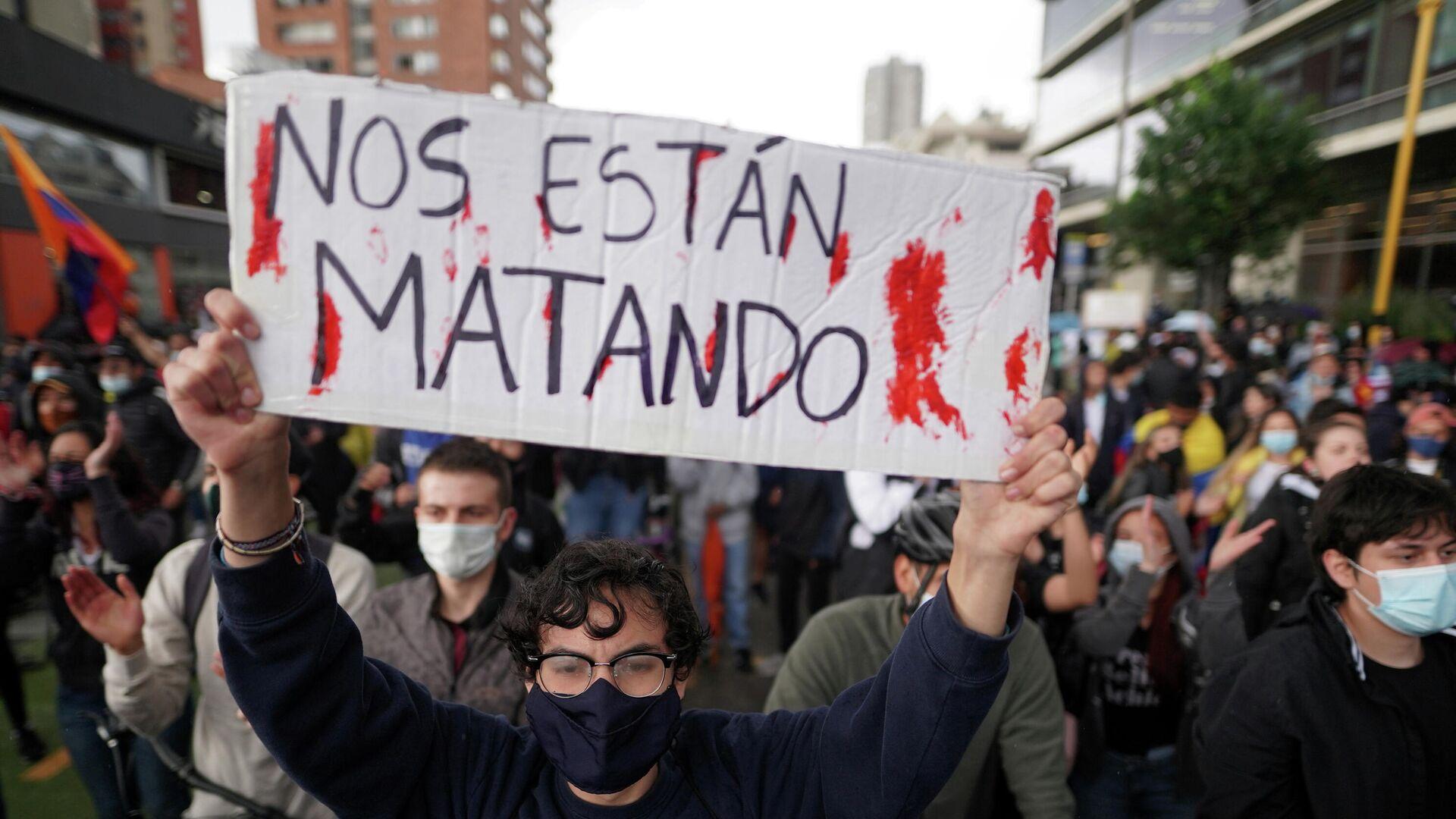 Un manifestante colombiano con un cartel que dice nos están matando. - Sputnik Mundo, 1920, 05.05.2021